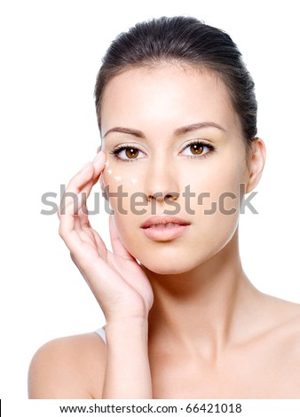 Portrait of young woman with fresh clean face with points of cream under the eye - stock photo
