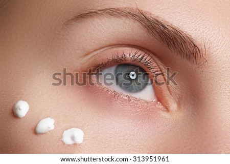 Portrait of young woman with fresh clean face with points of moisturizing  cream under the eye - stock photo