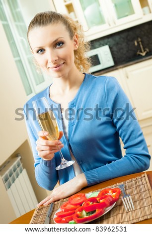 Portrait of young woman with glass of champagne, at home