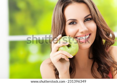 Portrait of young woman with green apple, outdoors, with copyspace - stock photo