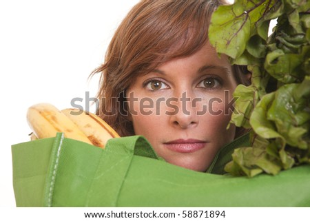 Portrait of young woman with green recycled bag filled with groceries - stock photo