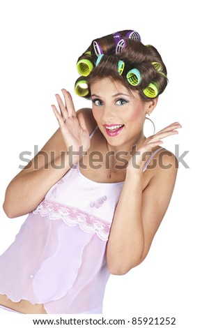 Portrait of young woman with hair-curlers - isolated on white background. Positive expression, hands near the face. - stock photo