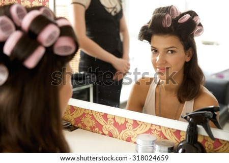 Portrait of young woman with hair curlers smiling - stock photo