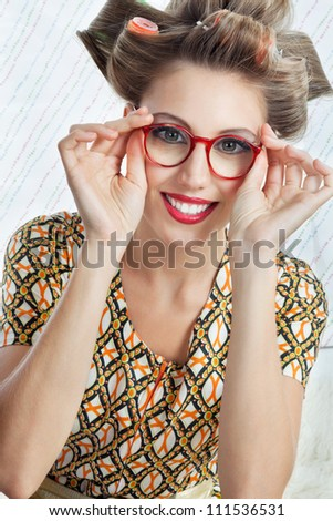 Portrait of young woman with hair curlers wearing red vintage eyeglasses - stock photo