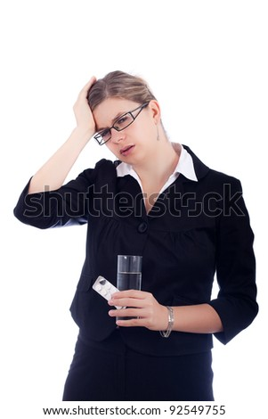 Portrait of young woman with headache, holding glass with water and tablets. Isolated on white background.