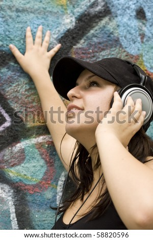 portrait of young woman with headphones at graffiti wall - stock photo