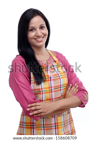 Portrait of young woman with kitchen apron against white background - stock photo