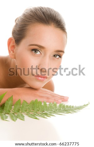 Portrait of young woman with leaf of fern - stock photo