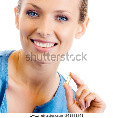 Portrait of young woman with Omega 3 fish oil capsule, isolated over white background - stock photo