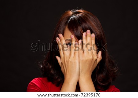 Portrait of young woman with only her eye visable through her hands - stock photo