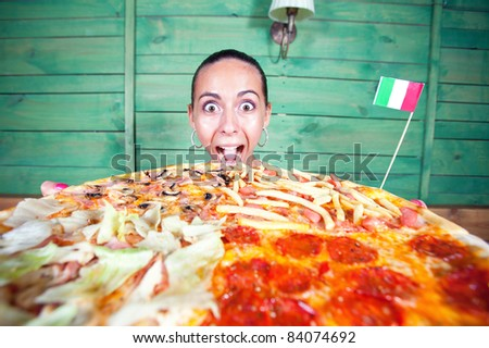 Portrait of young woman with pizza at kitchen - stock photo