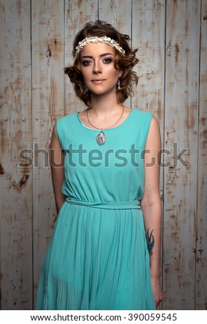 portrait of young woman with professional makeup and hairdo in summer dress and jewellery in wooden background