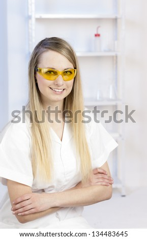 portrait of young woman with protective glasses in laboratory - stock photo