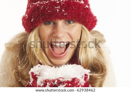 Portrait of young woman with red hat and gloves holding snow