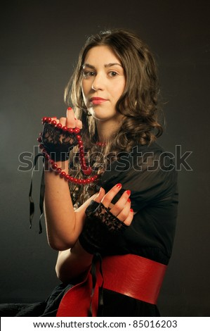 Portrait of young woman with red pearl and belt