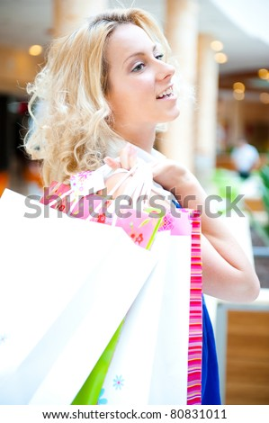 Portrait of young woman with shopping bags, smiling and walking indoor - inside modern mall - stock photo