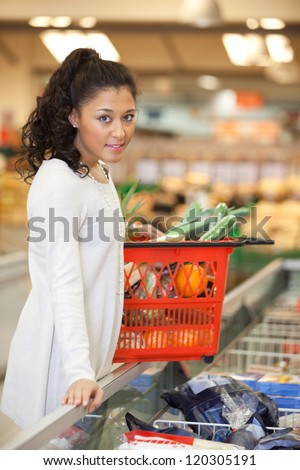 Portrait of young woman with shopping basket standing at checkout counter in supermarket - stock photo