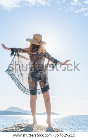 Portrait of young woman with straw hat  on the beach