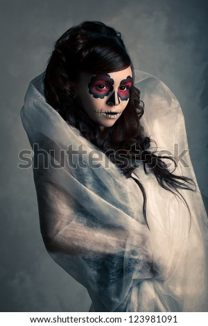Portrait of young woman with sugar skull make-up . Dramatic lighting.