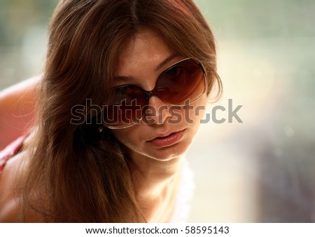 Portrait of young woman with sunglasses, window background - stock photo