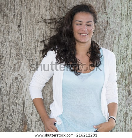 Portrait of young woman with the wind playing with her long hair. Trunk tree on background. She is dreaming with her eyes closed and big smile. - stock photo