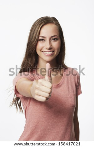 Portrait of young woman with thumbs up in studio - stock photo