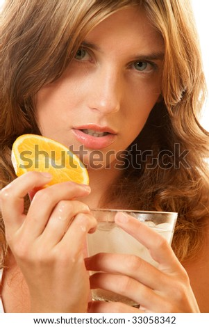 Portrait of young woman with water and slice of orange - stock photo