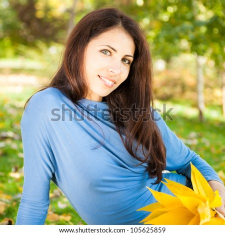 Portrait of young woman with yellow leaves in autumn park - stock photo