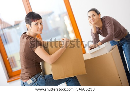 Portrait of young women packing up cardboard boxes. Looking at camera, smiling.