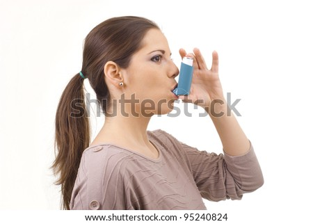 portrait of young women using asthma inhaler - stock photo
