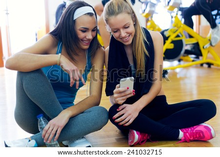 Portrait of young women using mobile phone in the gym. - stock photo