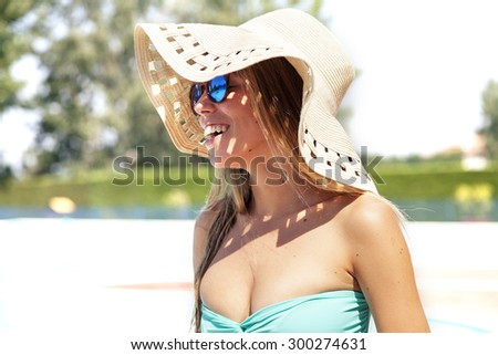 portrait of young women wearing hat and sunglasses by swimming pool - stock photo