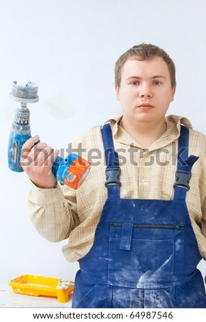 portrait of young worker with drill in hand - stock photo