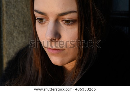 Portrait of young worried girl with big dark brown eyes looking down closeup