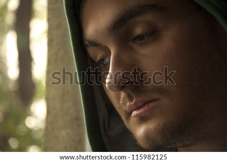Portrait of young worried man looking through window - stock photo