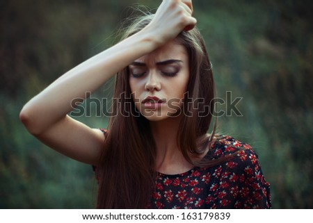 Portrait of young worried woman on the nature - stock photo