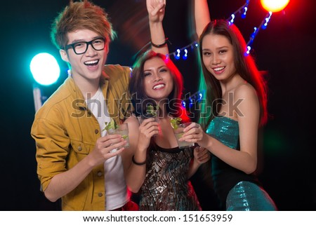 Portrait of youngsters partying in the club on the foreground