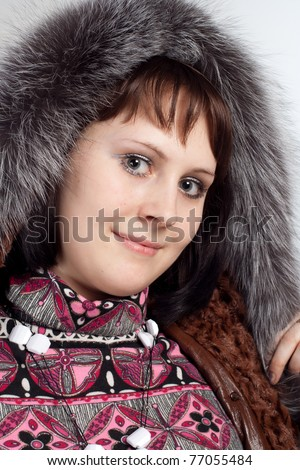 Portrait of youth woman in coat with fur neck isolated