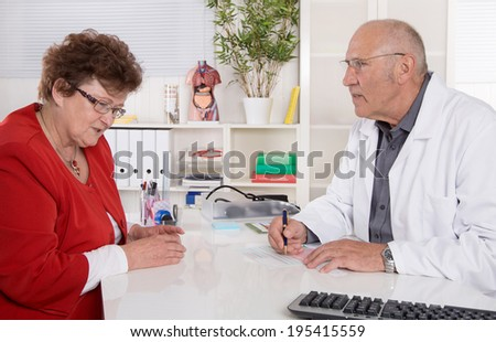 Portrait: older doctor with experience talking with senior woman sitting at desk. - stock photo