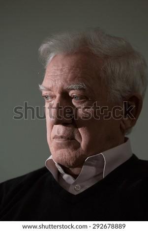 Portrait on grey background of sad elder man crying - stock photo