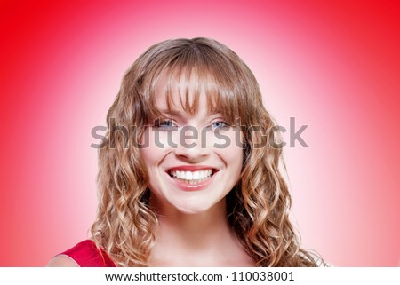 Portrait on the happy face of a smiling beautiful teen girl with blonde curly hair looking cheerful in a beauty clear and clean skin conceptual on red background - stock photo
