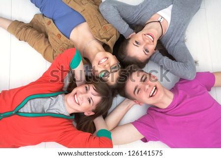 Portrait ot four studients having good time with laptop - stock photo