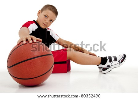 Portrait over white of young boy child basketball player sitting with ball relaxing.