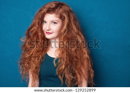 portrait picture of young beautiful ginger girl on blue background - stock photo