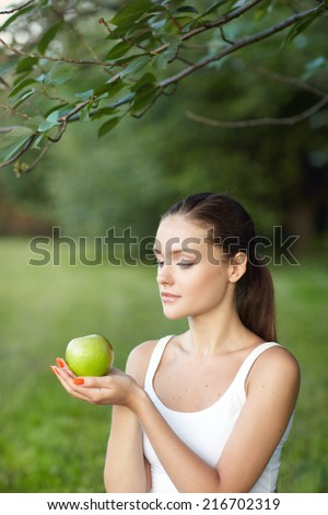 portrait pretty  long-haired woman hands yellow apple background summer park - stock photo