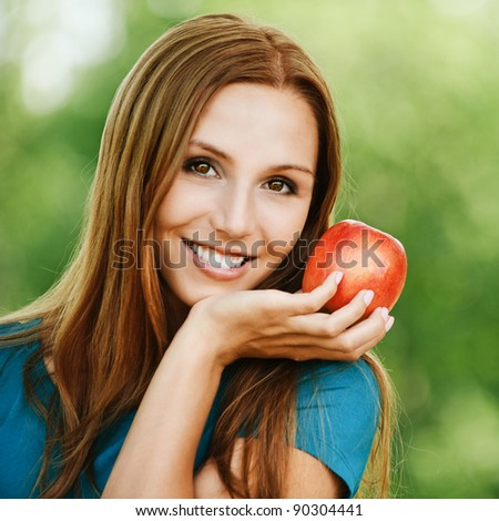 portrait pretty smiling woman vegetarian red apple hand background summer green park - stock photo