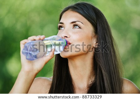 portrait pretty young woman background green summer park drinking water bottle - stock photo