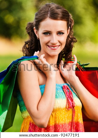 Portrait pretty young woman standing keeps shoulders shopping bags background summer green park - stock photo