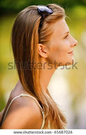Portrait profile of young beautiful woman against summer lake - stock photo