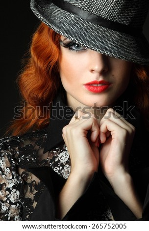 Portrait redhead, a young woman in hat. against a dark background. sexy look, lush red lips. fashion evening make-up. artistic hand gestures